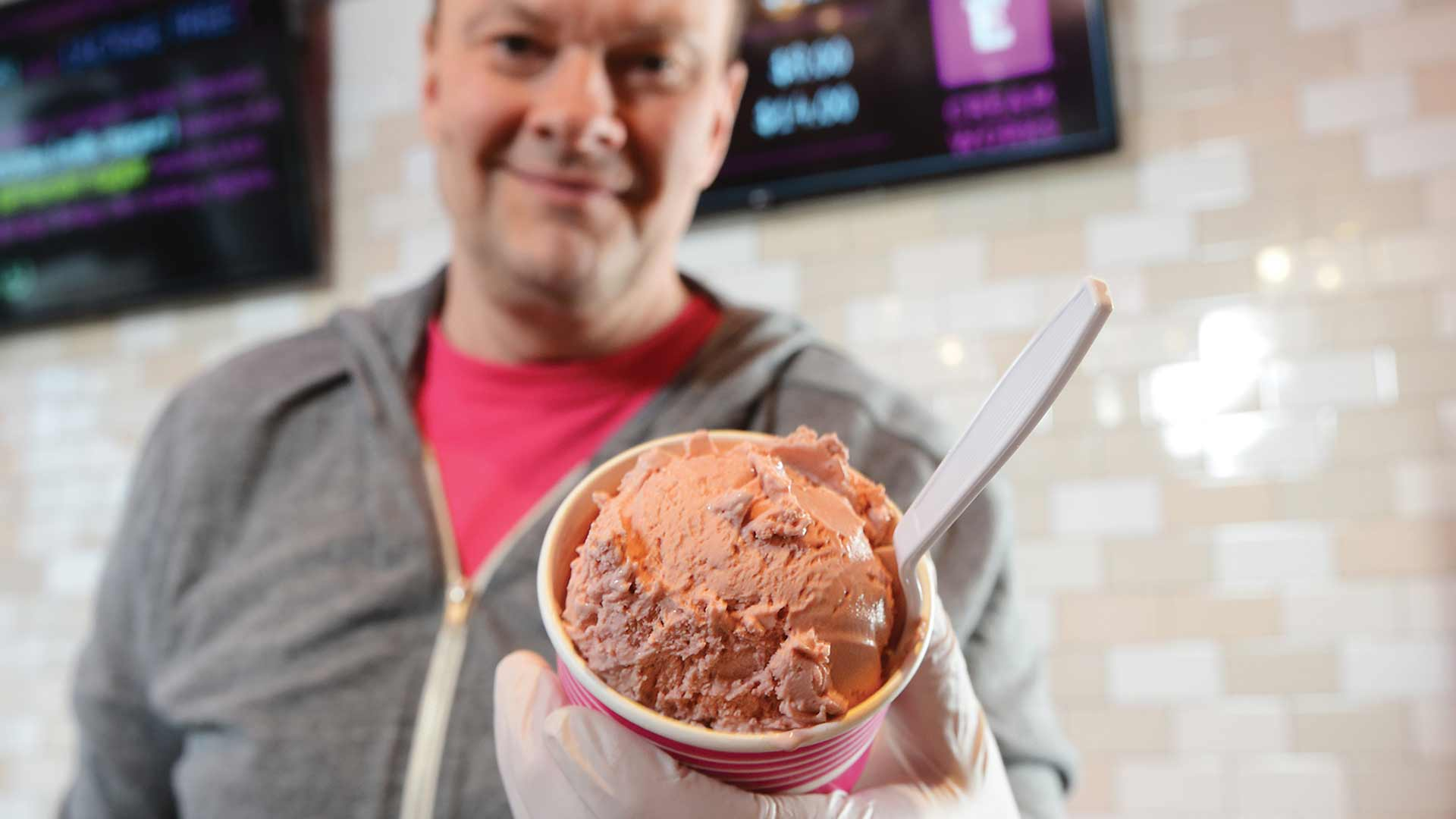 man holding cup of lactose-free ice cream